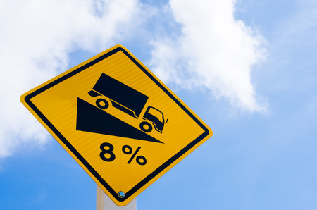 downgrade: Traffic sign. Down hill sign warning on blue sky and white cloud background. Copy space of transportation and travel concept.
