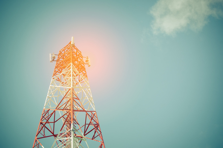 Copy space of telecommunication tower TV and radio antenna signal on blue sky and white cloud background. Vintage tone filter color style.