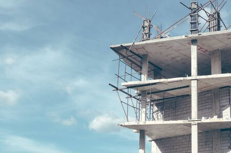scaffolds: Copy space of incomplete building construction site on blue sky and white cloud background. Building and business investment concept. Vintage tone filter effect color style. Stock Photo