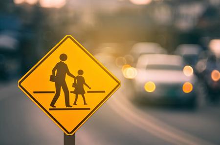 Señal de advertencia de zona escolar en carretera de tráfico de desenfoque con fondo abstracto de luz bokeh colorido. Copia espacio de transporte y concepto de viaje. Estilo de color de efecto de filtro de tono vintage. Foto de archivo