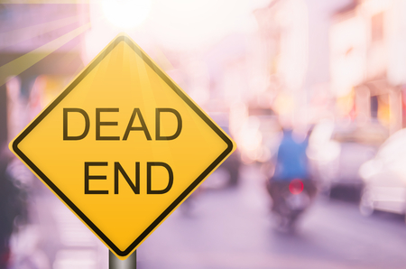 Dead end warning sign on blur traffic road with colorful bokeh light abstract background. Copy space of transportation and travel concept. Retro tone filter color style. Stock Photo