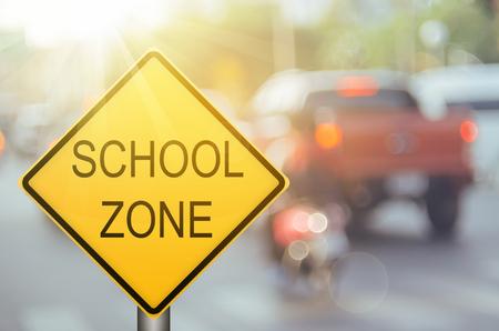 Señal de advertencia de la zona escolar en el camino del tráfico de la falta de definición con el fondo abstracto de la luz colorida del bokeh. Copie el espacio del concepto de transporte y viajes. Estilo de color de filtro de tono vintage. Foto de archivo