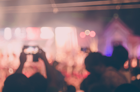 band bar: Blur people taking smart phone in night outdoor concert with colorful bokeh abstract background. Copy space of activity and lifestyle concept. Vintage tone filter effect color style.