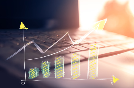 Business economic and technology working concept. Close up keyboard notebook window sunset light double exposure graph money stock trading up trend arrow bokeh background. Vintage filter effect color.