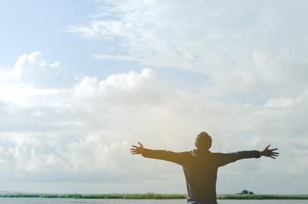 良い自由を感じ、概念冒険旅行します。幸せな男のコピー スペースは、川と青い空白い雲を背景に手を上げます。ビンテージ トーン フィルター効