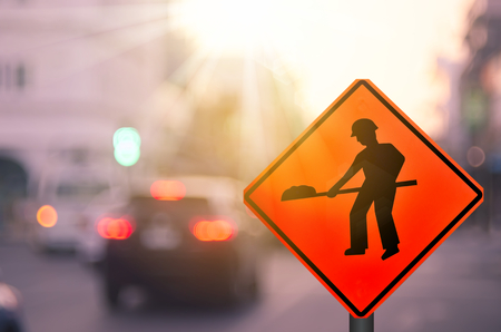 Construction warning sign on blur traffic road with colorful bokeh light abstract background. Copy space of transportation and travel concept. Retro tone filter effect color style.