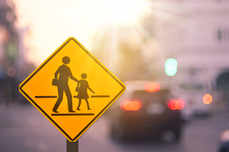 School zone warning sign on blur traffic road with colorful bokeh light abstract background. Copy space of transportation and travel concept. Vintage tone filter effect color style.