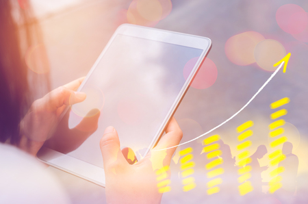 bullish market: Business economic technology working concept. Woman using smart phone tablet street double exposure graph money stock trading up trend arrow bar bokeh people background.Vintage tone filter effect color style