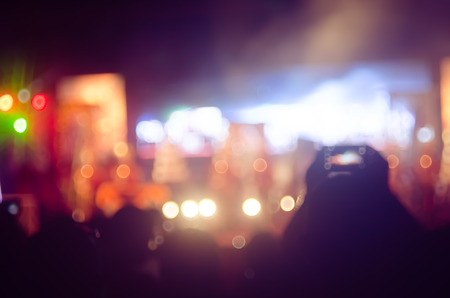 dancing club: Blur people taking smart phone in night outdoor concert with colorful bokeh abstract background. Copy space of activity and lifestyle concept. Vintage tone filter effect color style.