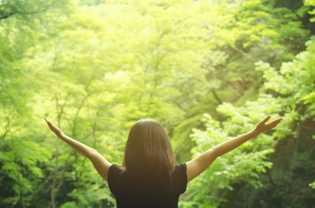Freedom feel good and travel adventure concept. Copy space silhouette woman rising hands in nature green leaf background in forest. Vintage tone filter effect color style. Stock Photo