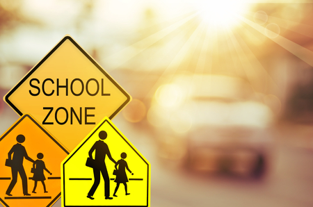 Set of School zone warning sign on blur traffic road with colorful bokeh light abstract background. Copy space of transportation and travel concept. Vintage tone filter effect color style.