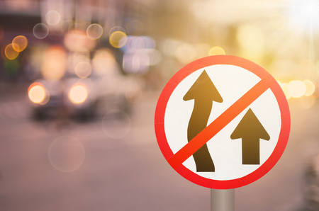 No Overtaking sign on blur traffic road with colorful bokeh light abstract background. Copy space of transportation and travel concept. Retro tone filter color style. Stock Photo