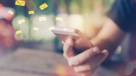 De vrouwenhand die slimme e-mailvlieg van de telefoon dubbele blootstelling gebruiken trekt bokeh bij koffie. Bedrijfseconomische technologie werken verbinden en reisavontuur ontspannen vakantieconcept. Vintage toonfilter kleurstijl.