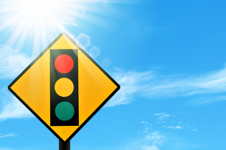 Traffic light warning sign on blue sky and sun light white clouds background. Copy space of transportation and travel concept.