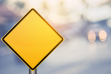 Empty yellow traffic sign on blur traffic road with colorful bokeh light abstract background. Copy space of transportation and travel concept. Retro tone filter effect color style. 版權商用圖片