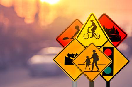 Set van verkeerswaarschuwingsbord op vervagen verkeersweg met kleurrijke bokeh lichte abstracte achtergrond. Kopieer de ruimte van transport- en reisconcept. Retro Toon filtereffect kleurstijl. Stockfoto