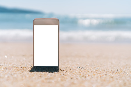 Smart phone on tropical sand beach with bokeh sun light wave texture background. Black copy space of technology and travel nature concept.