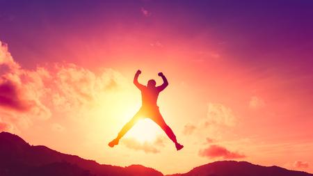 Glücklicher Mann, der an der Spitze des Berges mit abstraktem Hintergrund des Sonnenunterganghimmels springt. Freiheit Wohlfühl- und Sommerferienkonzept. Farbstil mit Vintage-Tonfiltereffekt. Standard-Bild