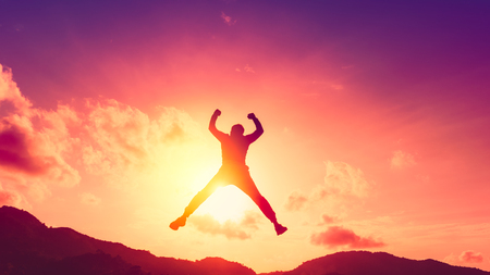Happy man jumping at top of mountain with sunset sky abstract background. Freedom feel good and summer vacation concept. Vintage tone filter effect color style. Reklamní fotografie
