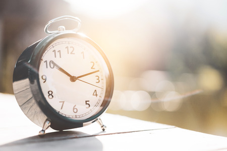 Clock on white wooden table with bokeh sunset light of lake abstract background. Copy space time and lifestyle concept. Vintage tone filter effect color style.