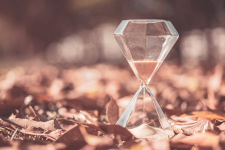 Hourglass on dry leaves with bokeh sun light abstract background. Copy space of time and life concept. Vintage tone filter effect color style. 写真素材