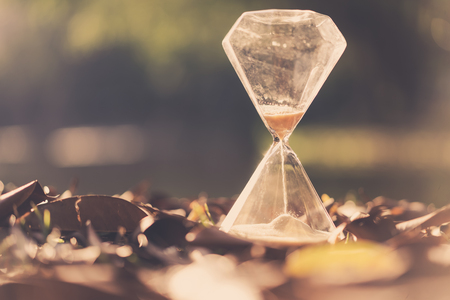 Hourglass on dry leaves with bokeh sun light abstract background. Copy space of time and life concept. Vintage tone filter effect color style. Standard-Bild - 122887358