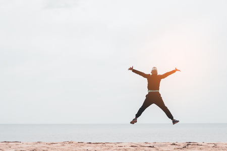 Happy man jumping at tropical sand beach background. Freedom feel good and summer vacation concept. Vintage tone filter effect color style.