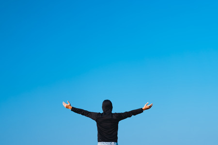 Copy space of man raise hands up on empty blue sky abstract background. Freedom feel good and summer vacation holiday concept. Vintage tone filter effect color style.