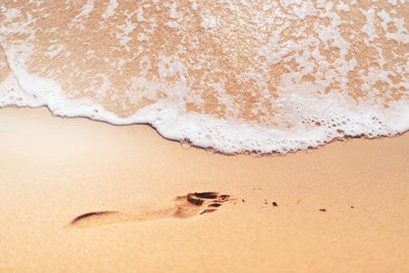 Impronta del piede sulla spiaggia di sabbia con fondo di struttura dell'estratto dell'onda liscia. Vacanze estive e concetto di vacanza di viaggio. Stile di colore effetto filtro tono vintage.