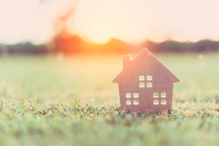 Copy space of home and life concept. Small model home on green grass with sunlight abstract background. Vintage tone filter effect color style. Imagens
