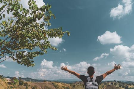 L'uomo zaino in spalla alza la mano in cima alla montagna con cielo blu e nuvole bianche sfondo astratto. Copia l'avventura di viaggio della libertà dello spazio e sentiti bene il concetto. Stile di colore effetto filtro tono vintage.