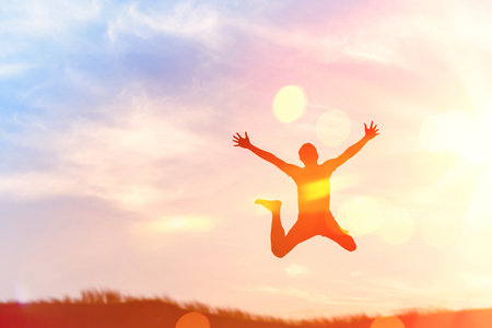 Happy man jumping at top of mountain with sunset sky abstract background. Freedom feel good and summer vacation concept. Vintage tone filter effect color style.