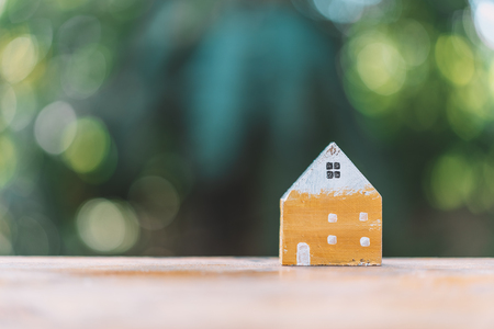 Small model house on wooden table with nature green bokeh sunlight abstract background. Copy space of business finance and life family concept. Vintage tone filter effect color style.