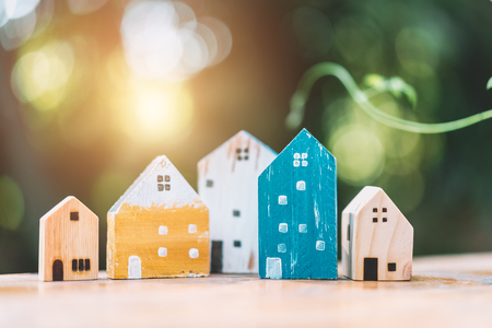 Small model houses on wooden table with nature green bokeh sunlight abstract background. Copy space of business finance and life family concept. Vintage tone filter effect color style.