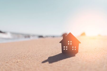 Small home model on sunset beach sand texture background. Copy space of family lifestyle and business real estate concept. Vintage tone filter effect color style.