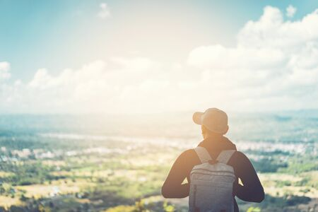 Backpacker man standing at top of mountain looking view landscape with blue sky white cloud abstract background. Copy space travel adventure holiday and freedom feel good concept. Vintage tone color.