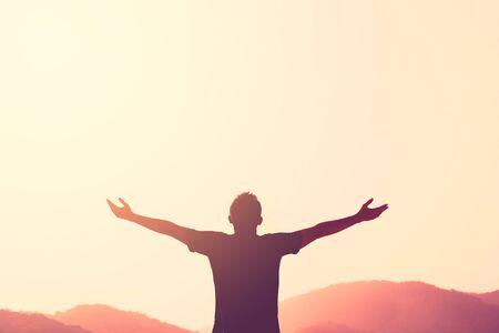 Copiez l'espace de la main de l'homme s'élevant au sommet de la montagne et du coucher du soleil abstrait. Concept d'aventure de voyage de liberté et de victoire d'affaires. Style de couleur d'effet de filtre de ton vintage.