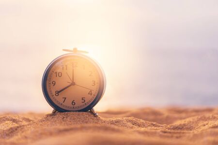 Clock on sand beach in morning suns light with smooth wave background. Copy space of time and summer holiday concept. Vintage tone filter effect color style. 版權商用圖片