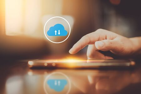 Woman hand using smart phone with cloud icon abstract background at coffee shop. Technology business and modern lifestyle concept. Vintage tone filter effect color. Stock Photo