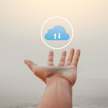 Man open hand raise up on sky background with cloud icon abstract at tropical beach.  Freedom feel good and technology business concept. Vintage tone filter effect color style. Stock Photo