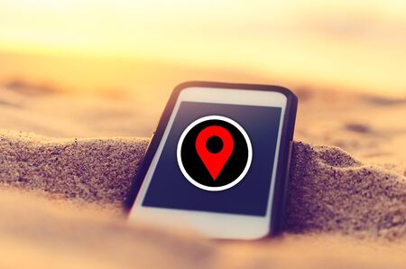 Smart phone and sand sunset beach with red navigator gps location abstract background. Copy space of technology travel vacation and business online concept. Vintage tone filter effect color style.