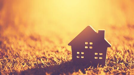 Copy space of home and life concept. Small model home on green grass with sunlight abstract background. Vintage tone filter effect color style. Stock Photo