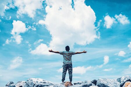 Man raise hand up at top of rock on blue sky and white cloud abstract background. Freedom feel good and travel adventure vacation concept. Vintage tone filter effect color style. Stockfoto