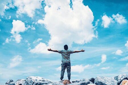 Man steek hand omhoog op de top van rots op blauwe hemel en witte wolk abstracte achtergrond. Vrijheid voel je goed en reis avontuur vakantie concept. Vintage toonfilter effect kleurstijl. Stockfoto