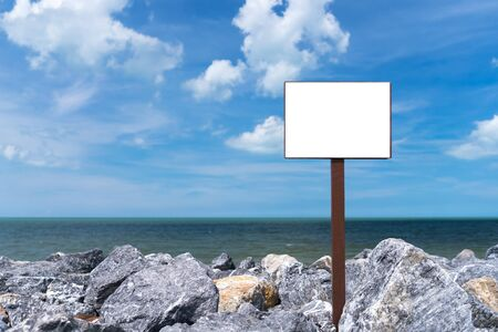 Copy space of old wooden white sign at rock beach with blue sky and white cloud abstract background.