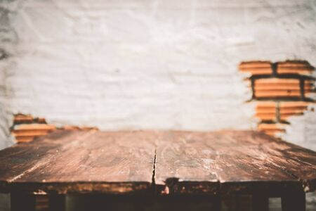 Copy space of old wooden table top on brown stone wall texture abstract background. Vintage tone filter effect color style.