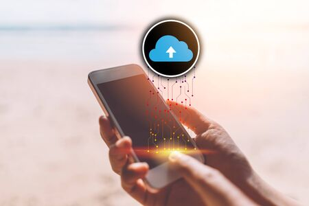 Woman hand using smart phone with cloud icon at tropical sunset beach background. Copy space of technology business and travel holiday concept. Vintage tone filter effect color style.