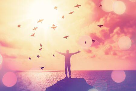 Kopieer de ruimte van de mens steek de hand omhoog op de avondrood op het strand en het eiland met dubbele belichting vogels vliegen kleurrijke bokeh abstracte achtergrond. Vrijheid en reizen avontuur concept. Vintage toonfilter kleurstijl.