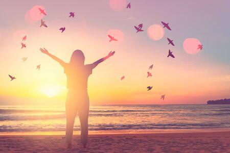 Kopieer de ruimte van de vrouw steek de hand omhoog op de avondrood op het strand en het eiland met dubbele belichting vogels vliegen kleurrijke bokeh abstracte achtergrond. Vrijheid en reizen avontuur concept. Vintage toonfilter kleurstijl. Stockfoto