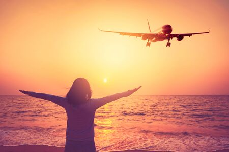 Airplane flying over woman rise hand up on sunset sky at beach and island background. Freedom travel adventure and transportation business concept. Vintage tone filter effect color style.